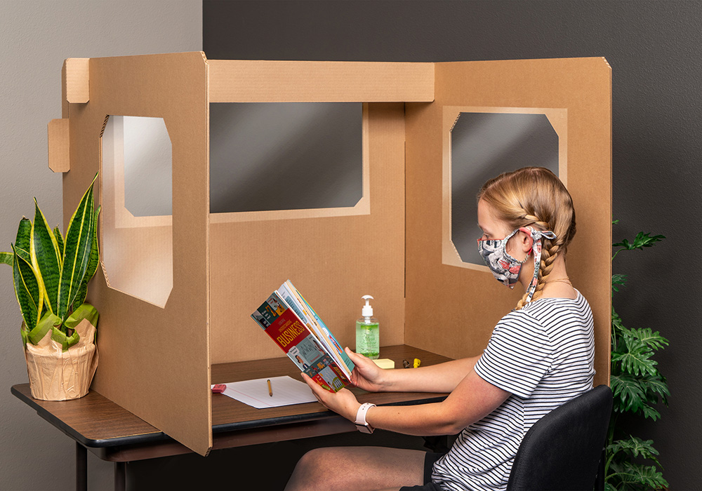 student with braided hair reading an usborne books & more business book at a desk with an ECORR Desk Divider keeping her safe